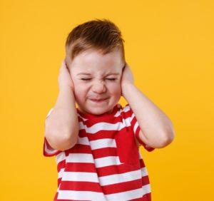 sensitive boy covering ears